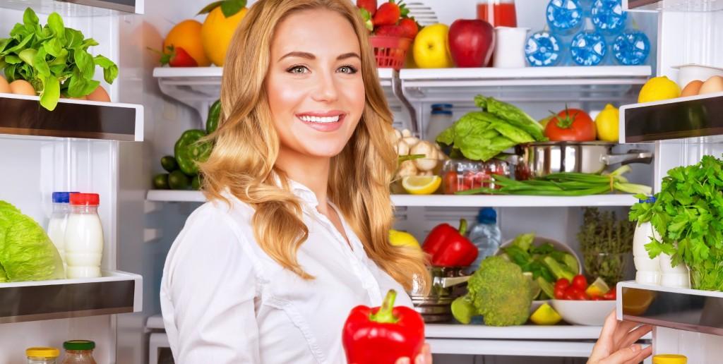 Woman chosen milk in opened refrigerator, cool new fridge full o
